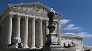 A lone police officer stands in front of the US Supreme Court amid the coronavirus outbreak