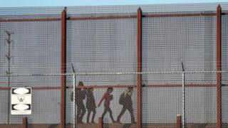 Migrants walk together along the US-Mexico border wall near El Paso on 4 June 2019