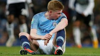 Kevin de Bruyne sits on the turf after his injury