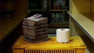 A pile of bolivar notes is stacked up next to a toilet roll
