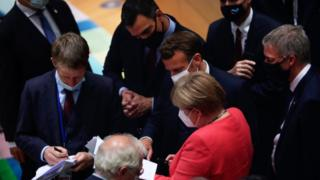 German Chancellor Angela Merkel (C, down) speaks with French President Emmanuel Macron (C) and Spanish Prime Minister Pedro Sanchez (C, up) during a round table meeeting at an EU summit over a post-virus economic rescue plan in Brussels, on July 20, 2020.