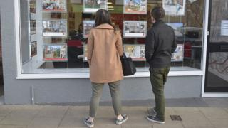 Young people looking in an estate agents' window