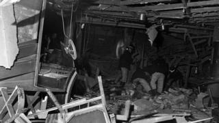 Firefighters search through the wreckage after a bomb went off in Birmingham