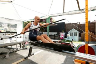 A sprint canoeist trains with equipment in his garden