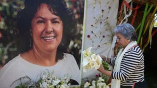 Una mujer deja flores antes un mural sobre Berta Cáceres