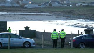 Police officers at the County Down beach where a body has been found