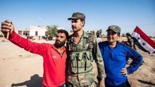 תושבים מקדמים בברכה כוחות ממשלת סוריה כשהם מגיעים לכניסה המערבית של העיירה טל תמר