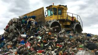 Landfill compactor vehicle on top of large pile of landfill