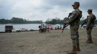 Colombian marines stand guard along the Mira river in Imbili, Tumaco Municipality, in the Colombian department of Narino near the border with Ecuador, on April 15, 2018.