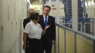 David Cameron being shown round a prison