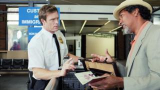 Un policía revisa el pasaporte de un turista
