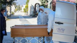 Undertakers wearing protective clothing carry a coffin in a cemetery in Bergamo