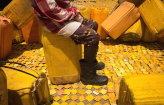 Someone sitting on a jerry can on some yellow tapestry created by artist Serge Attukwei Clottey on a road in La - Accra, Ghana