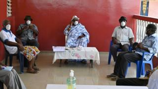 Elders have a meeting about coronavirus at a village in the Ivory Coast