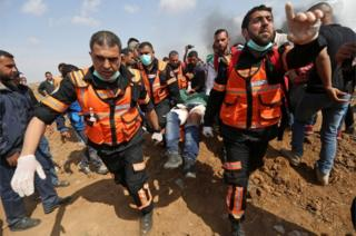 Palestinians carry an injured man during clashes with Israeli security forces near the eastern border of the Gaza Strip
