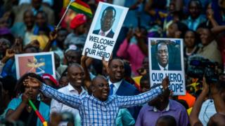 """Supporters hold banner, wave Zimbabwean national flag and cheer as they gather to welcome Zimbabwe""""s incoming President Emmerson Mnangagwa upon his arrival at Zimbabwe""""s ruling Zanu-PF party headquarters in Harare on November 22, 2017."""