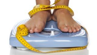 Una persona parada sobre una balanza