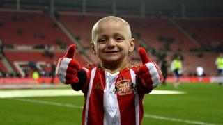 Bradley Lowery gives a thumbs-up on the Stadium of Light pitch
