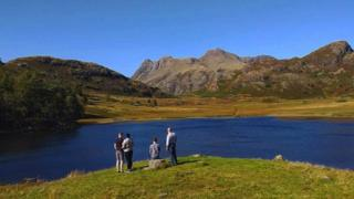 Four tourists admire the view (hills and lake) in the Lake District