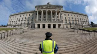 A security guard stands on the steps of Stormont's Parliament Buildings