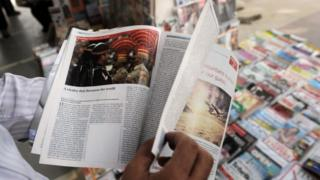 """In this photograph taken on May 24, 2011, an Indian resident reads a censored issue of the Economist magazine at a road-side stall in New Delhi. Anyone distributing a map the Indian government deems to be """"wrong"""" could be liable for a billion-rupee ($15 million) fine and jail time under a new draft bill."""