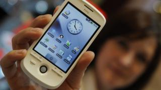 A woman holding an HTC phone