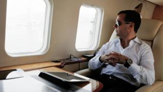 Dmitry Medvedev looks through a helicopter's window, with an iPad on a table in front of him