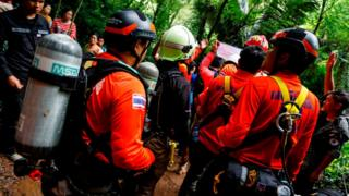 Navy divers assemble in the forest to conduct a search for a group trapped inside a Thai cave
