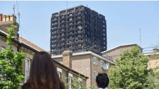 people looking at burnt out grenfell tower