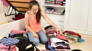 Garota organiza suas roupas em uma pilha no chão