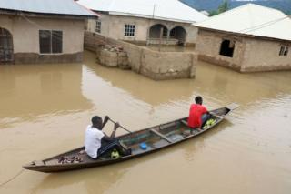 Residents steer a dugout canoe past flooded houses following heavy rain in the Nigerian town of Lokoja, in Kogi State, on September 14, 2018.