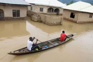 Становници се уз помоћ кануа крећу поред поплављених кућа после јаких киша у месту Локоја, држави Коги у Нигерији, 14. септембра 2018. године