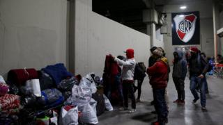 Homeless people look through bags of donated clothes at River Plate stadium in Buenos Aires, Argentina on 3 July 2019
