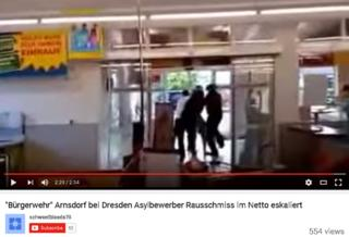 screengrab of video where men are bundling somebody out the door of a supermarket