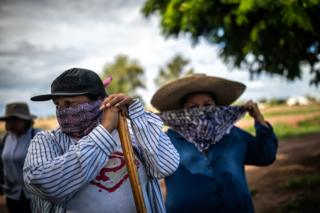 Juana Escalante, left, gets ready for a search near a farm where a horseman reported the smell of decomposition