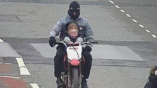 child on bike with balaclava-clad rider