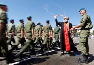 Un sacerdote ortodoxo bendice a un grupo de paracaidistas rusos en una base militar en la ciudad de Stávropol, en medio de las celebraciones del Día del Paracaidista en Rusia.