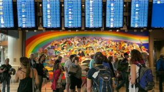 Pessoas olham para telas de chegadas e partidas em aeroporto