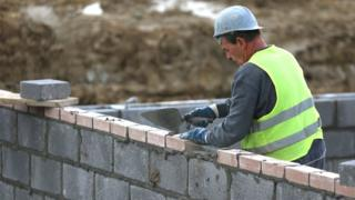 File photo of a construction worker laying bricks at a housing development
