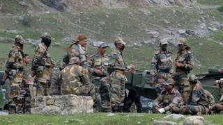 Indian army soldiers rest next to artillery guns at a transit camp before heading to Ladakh, 16 June