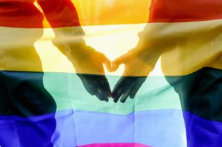 A couple make a heart symbol with their hands behind a pride flag