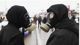 Two protesters in gas masks.