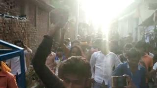 A screen grab from the video where a woman is being paraded surrounded by a mob