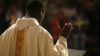 Catholic priest wey dey pray