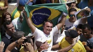 "Congressman Jair Bolsonaro holds a Brazilian flag during a protest against Brazil""s President Dilma Rousseff, part of nationwide protests calling for her impeachment, in Brasilia, Brazil, March 13, 2016"