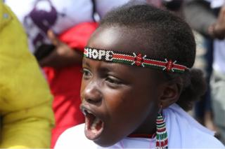 """A girl wearing a beaded headband with the word """"hope"""" weaved into is seen shouting. Her expression is passionate."""