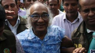 Bangladeshi security personnel escort Shafik Rehman (centre) at a court following his arrest in Dhaka (16 April 2016)