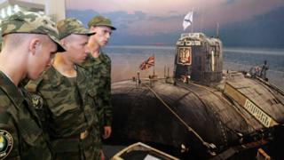 Marinos rusos frente a una fotografía del submarino Kursk.