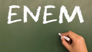 """Quadro escolar com a palavra """"Enem"""" escrita com giz; no canto inferior direito, uma mão com um giz"""