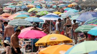 A packed Malvarrosa beach during a hot day in Valencia, Spain